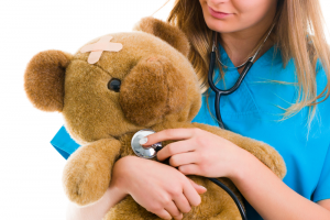 Lady takes care of examining her teddy bear