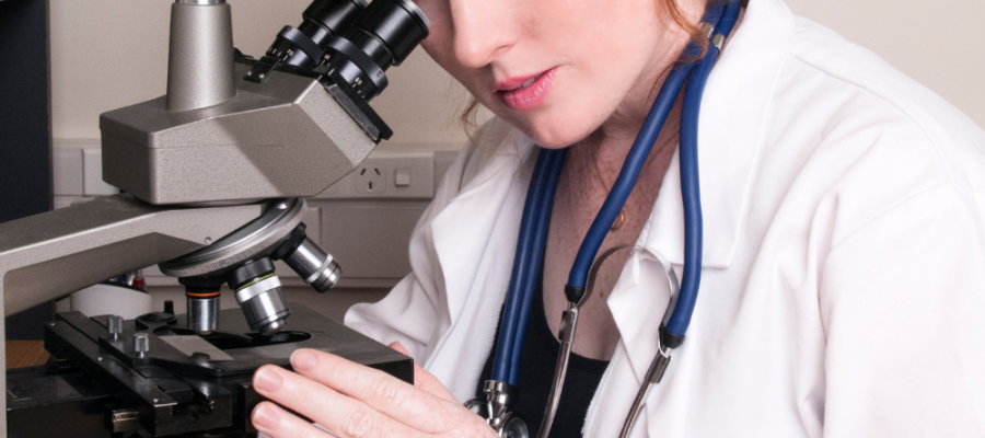 female doing some research with a microscope